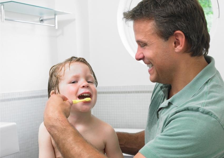 Dientes amarillos en niños | Padre cepillando dientes a hijo.