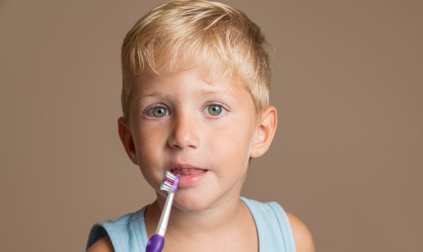 Dientes amarillos en niños: causas, prevención y tratamiento | Niño sujetando cepillo de dientes