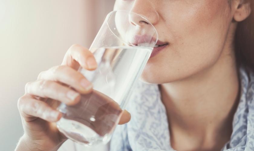 Salud bucodental y esclerosis múltiple: mujer bebiendo agua para evitar sequedad bucal.