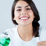 Los colutorios no sustituyen al cepillado dental: mujer sosteniendo bote de enjuague bucal.